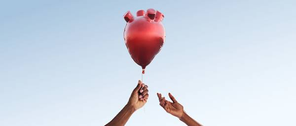 A hand passing a heart-shaped balloon to another hand