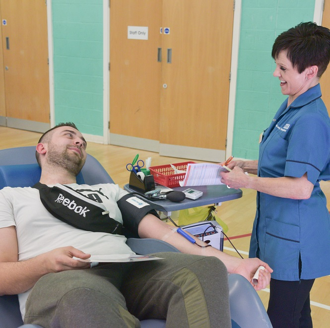 A blood donor sits in a reclined donor chair