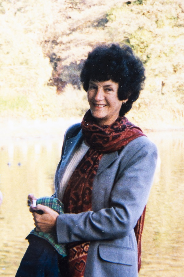 An image of Ann Butler smiling, at the side of a lake