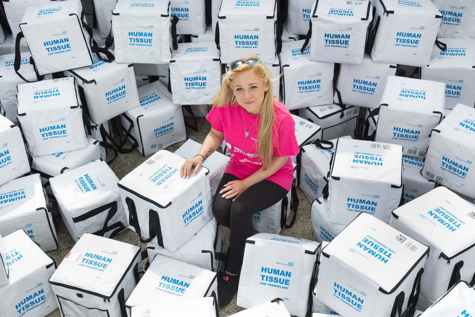 Transplant recipient Izzy Sewell sits amongst human tissue transplant boxes