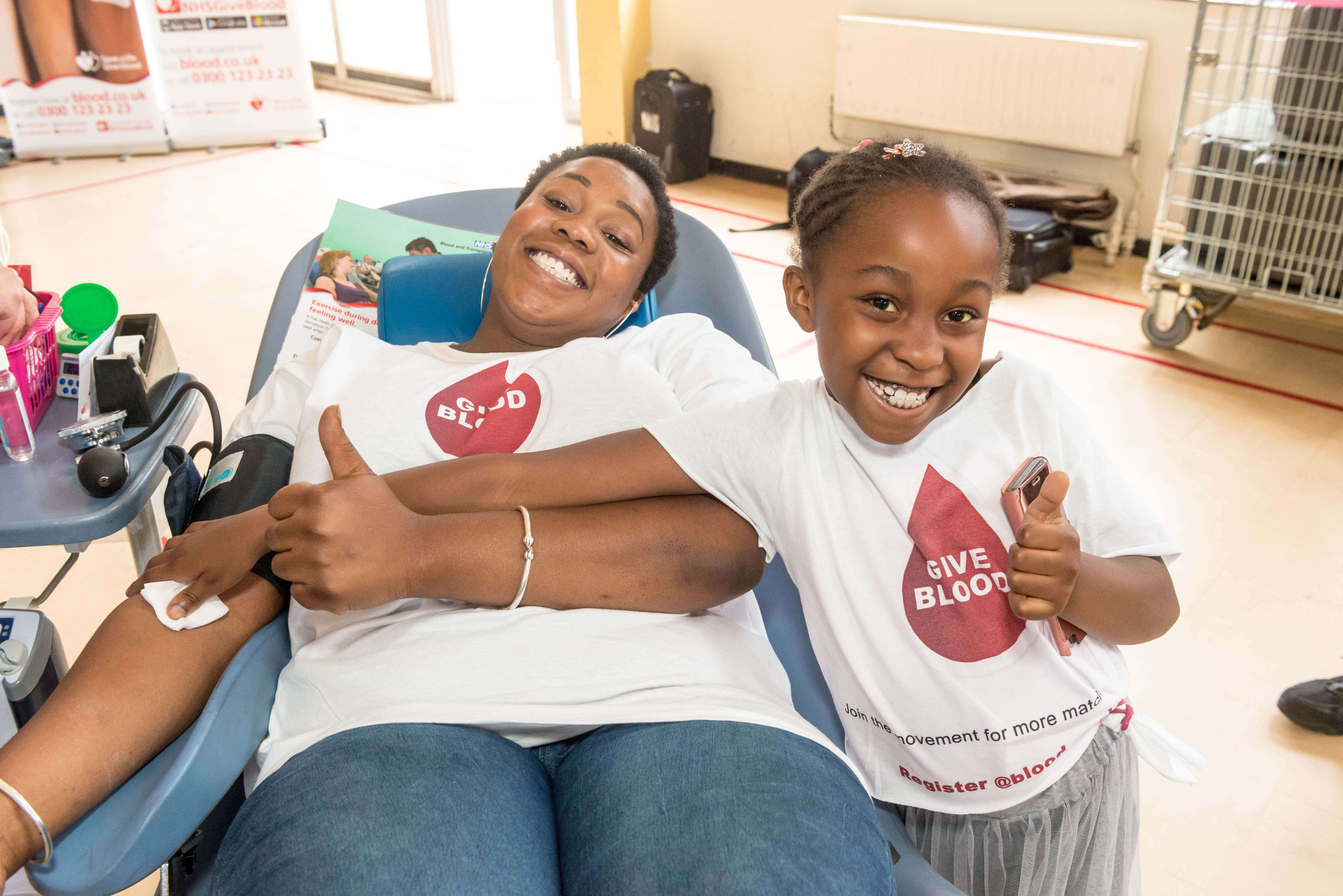 Lisa donates blood while daughter Miai gives the thumbs up