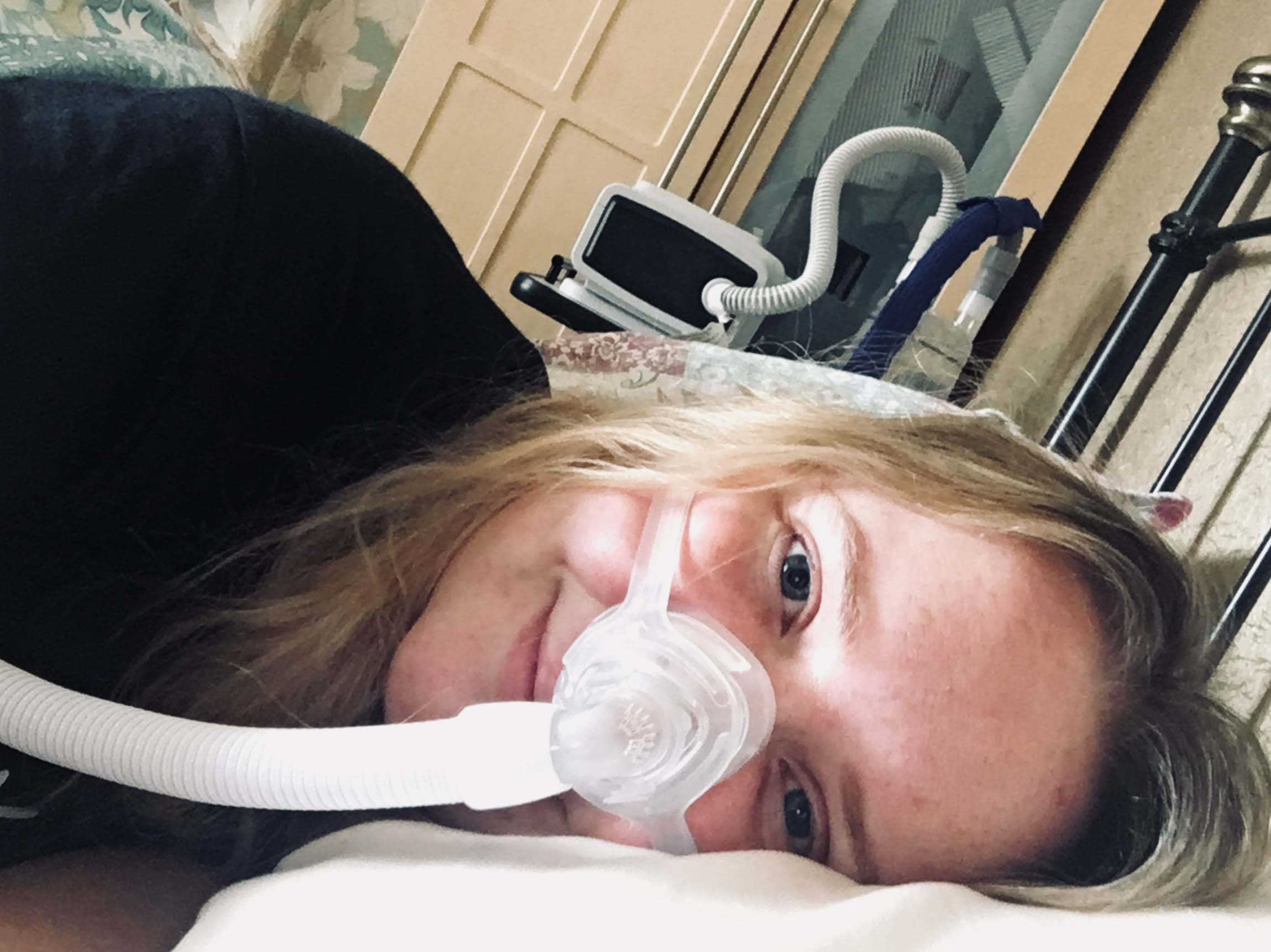 Laura Beattie smiling, wearing an oxygen mask