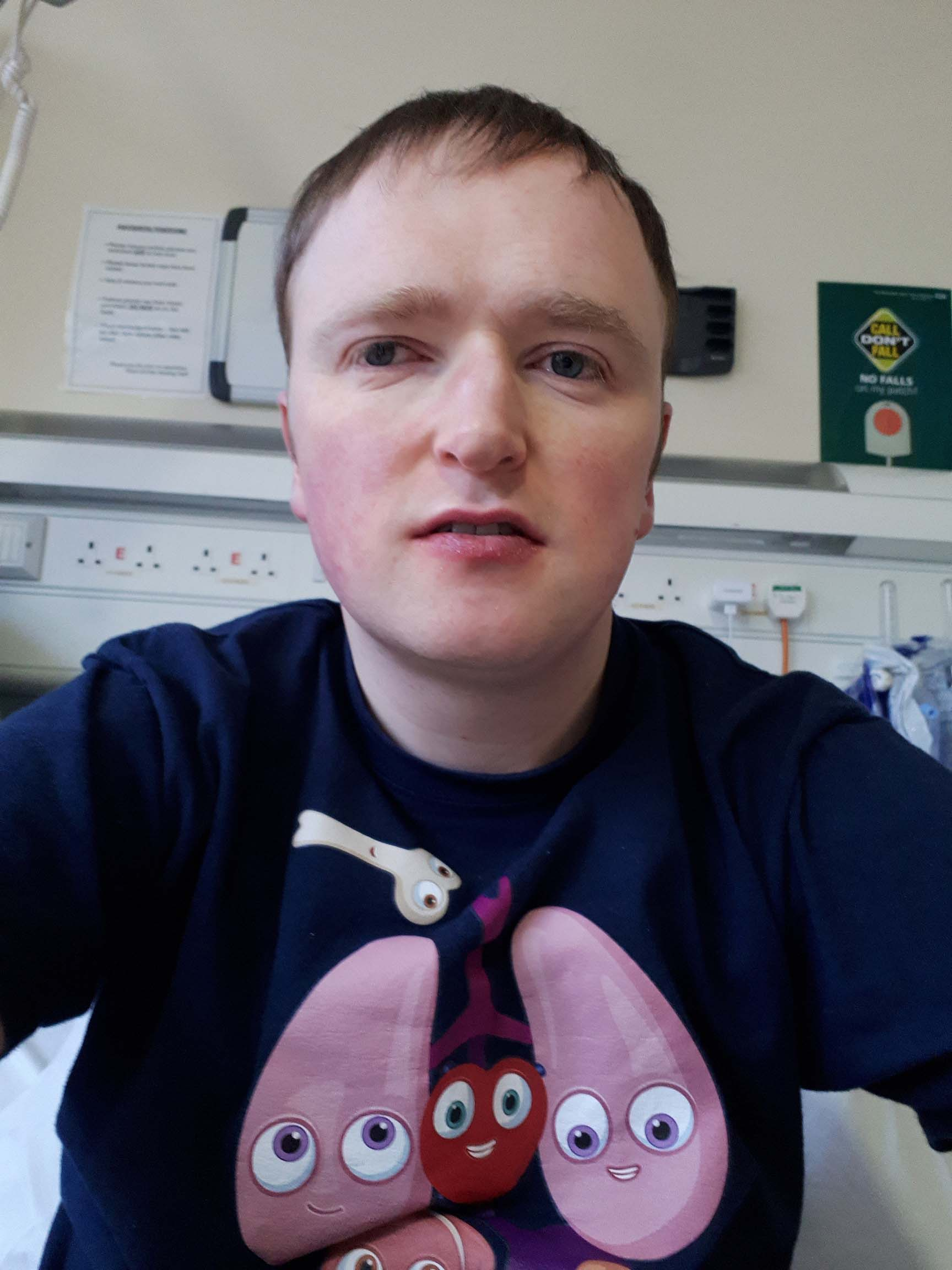 Patrick sits on a hospital bed wearing an organs t-shirt