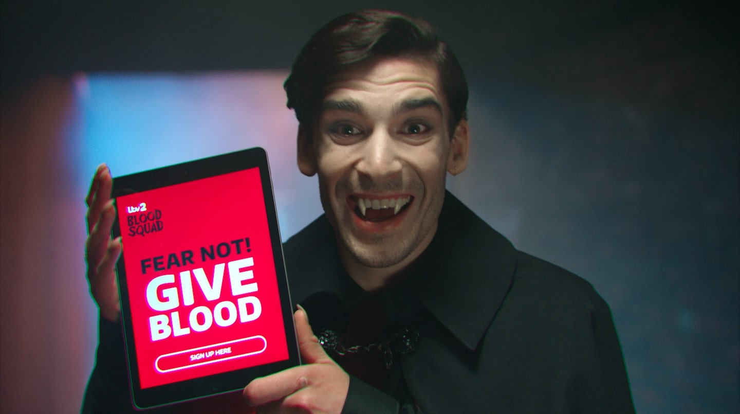 Colin the vampire holds a computer tablet