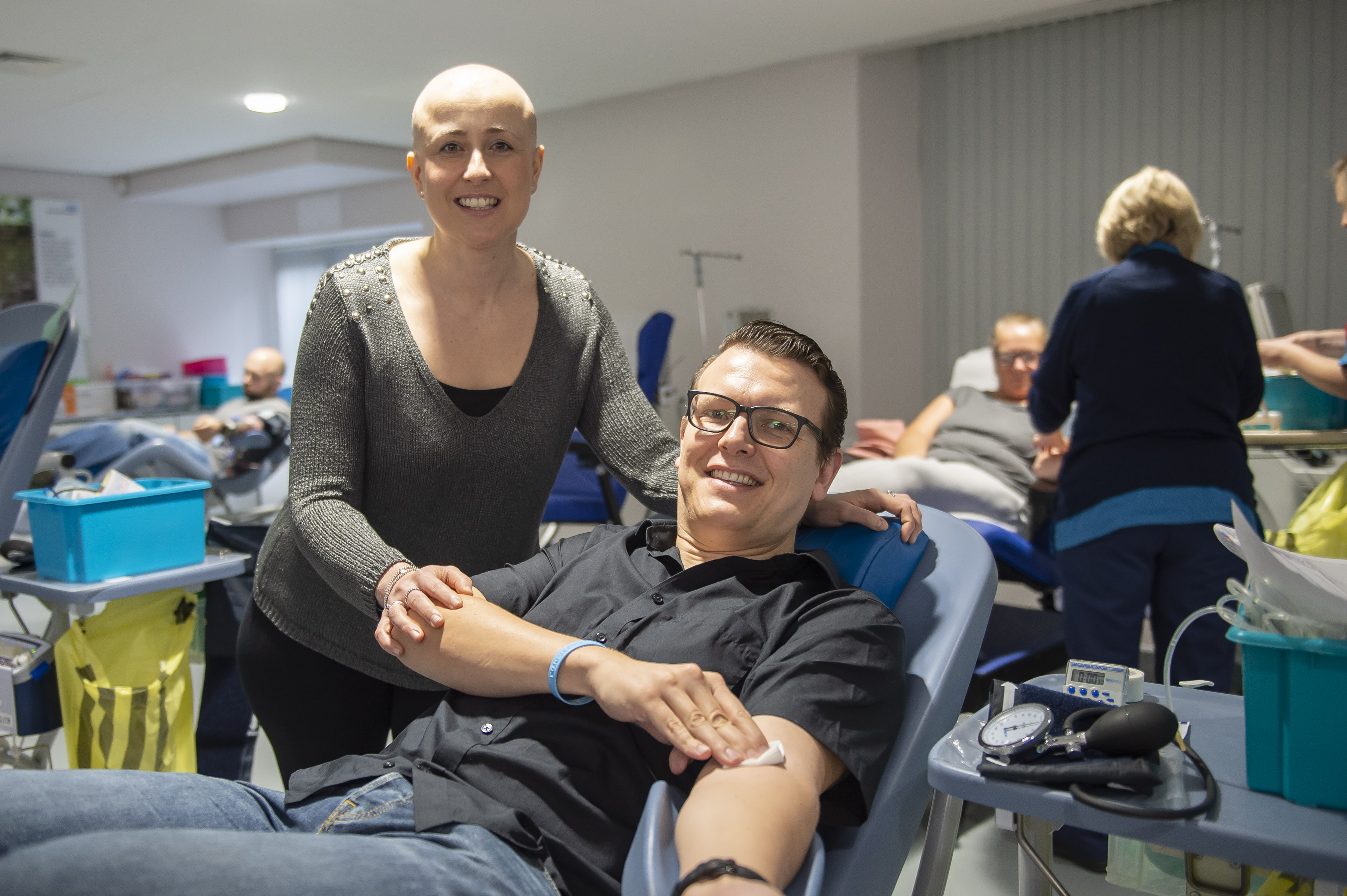 Hayley Perks watches her husband, Aiden donate blood