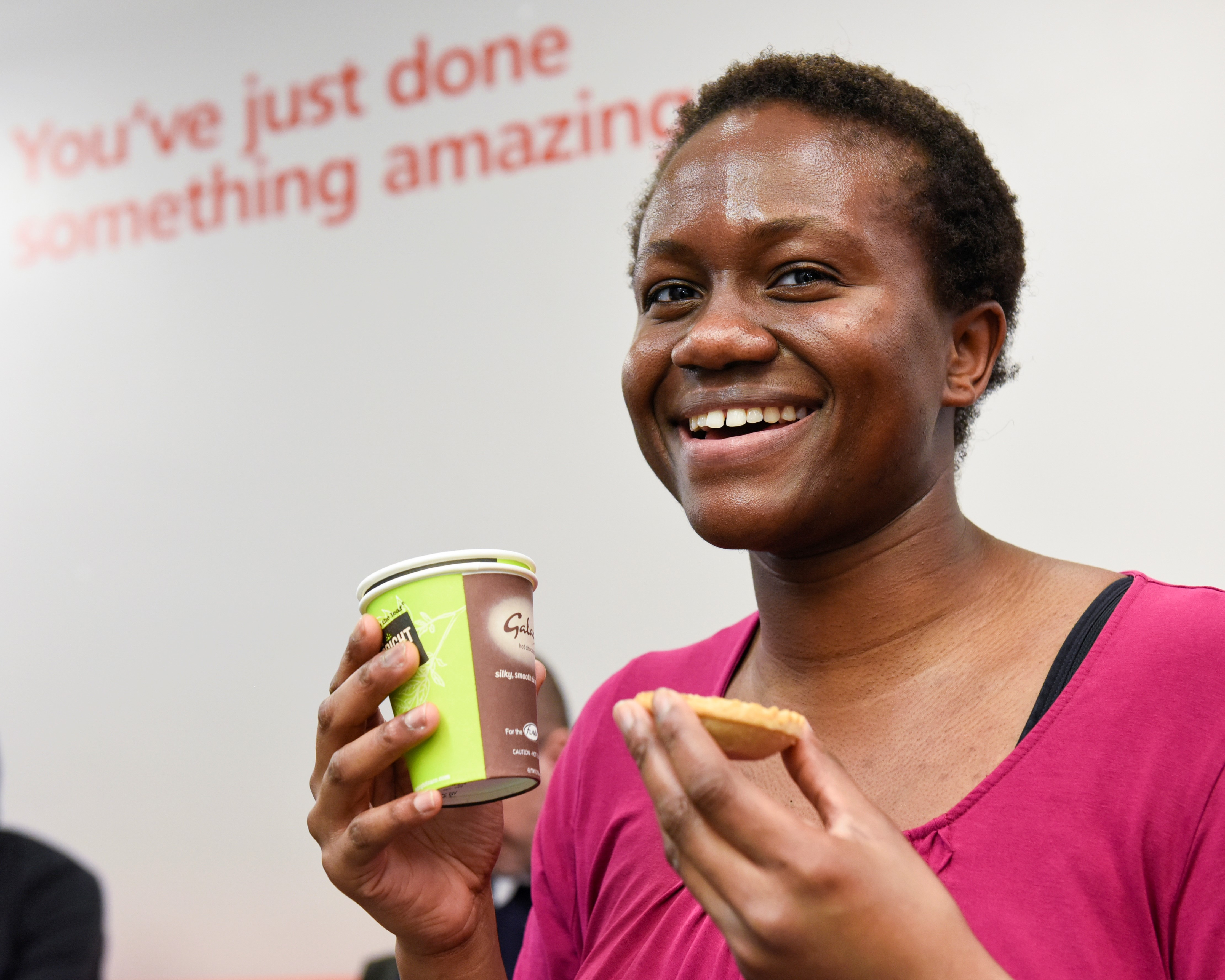 a woman has a drink and biscuit after donating