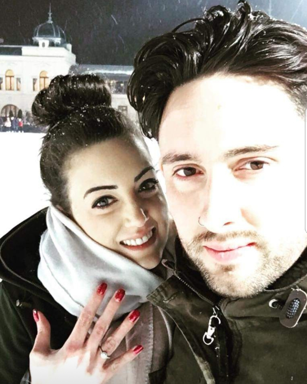 Emily poses with her engagement ring alongside Sam in the snow in Budapest
