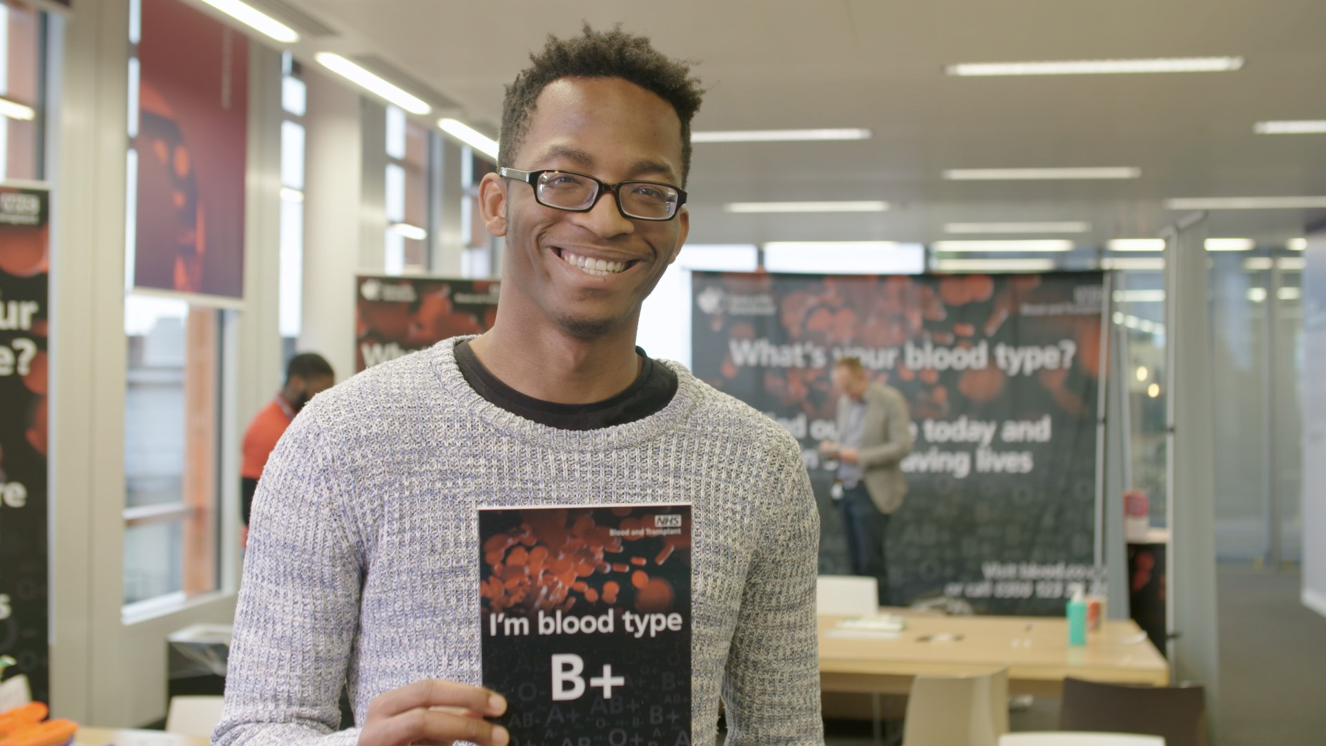 "A young man holds a card that says, ""I'm blood type B+"""