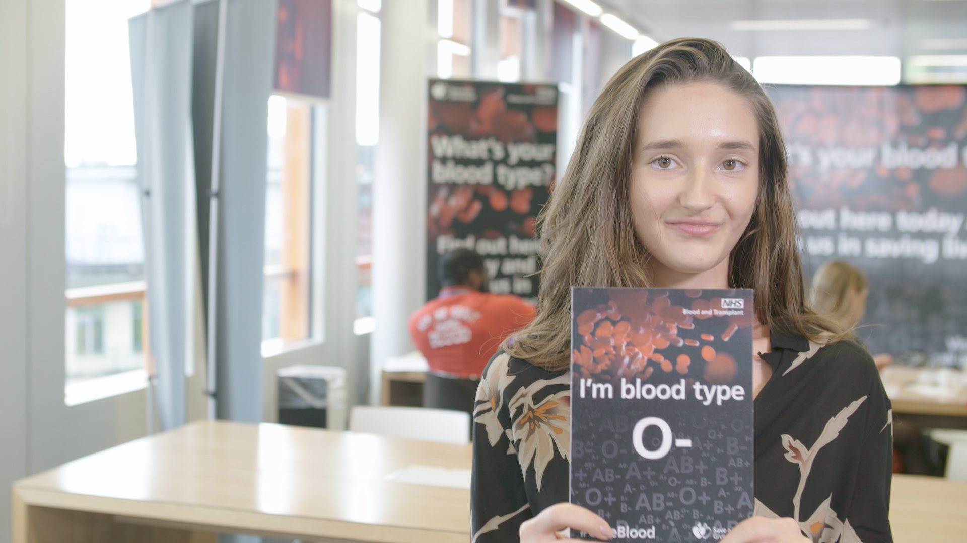 "A young woman holds a card that says, ""I'm blood type O+"""