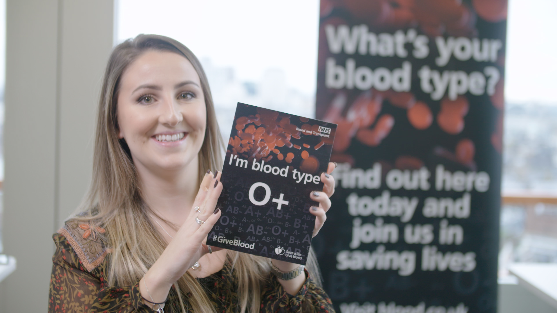"""A young woman holds a sign that says, """"I'm blood type O+"""""""