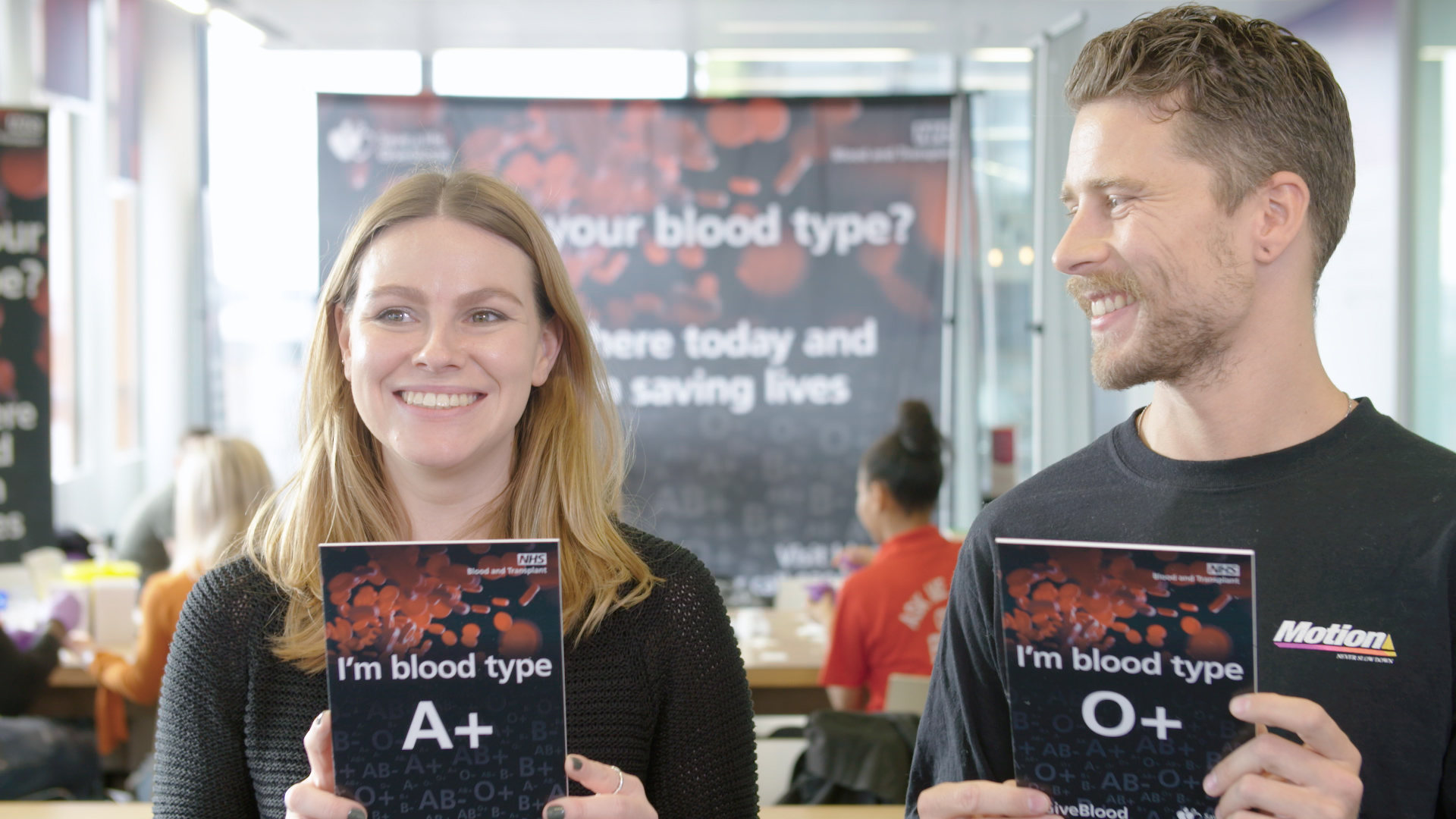Two young people hold cards with their blood type on