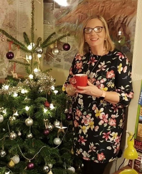 Donna stands next to a Christmas tree with a hot drink