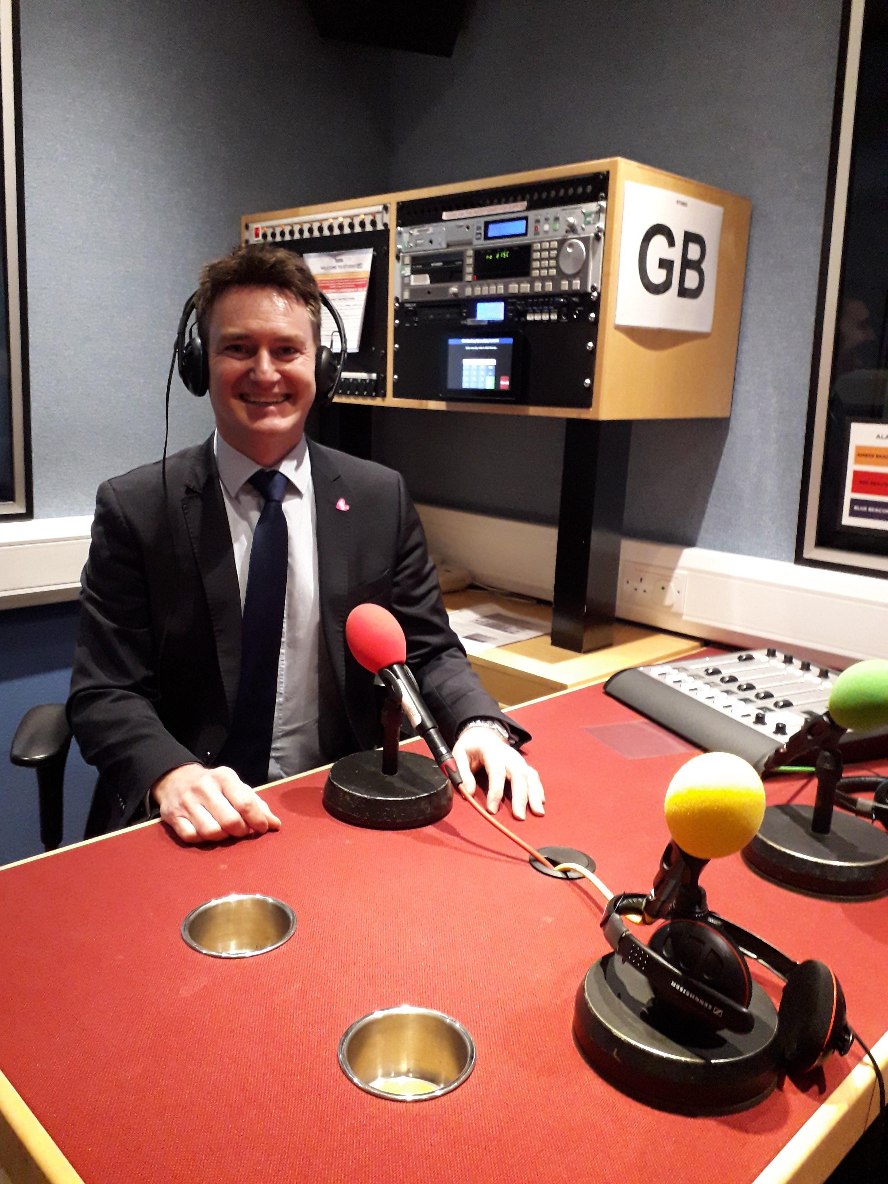 Anthony wearing headphones in a radio studio