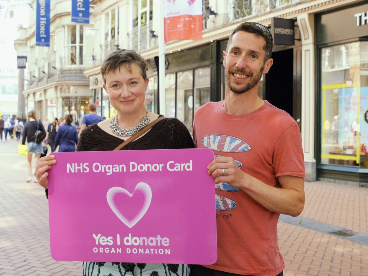 A man and a woman holding up a large Organ Donor Card and smiling
