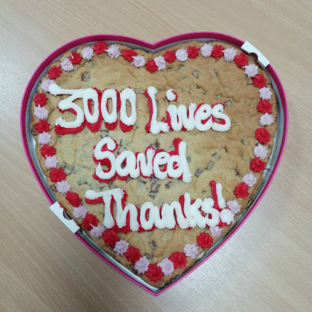 A large, heart-shaped cookie with icing that reads, '3,000 lives saved. Thanks!'