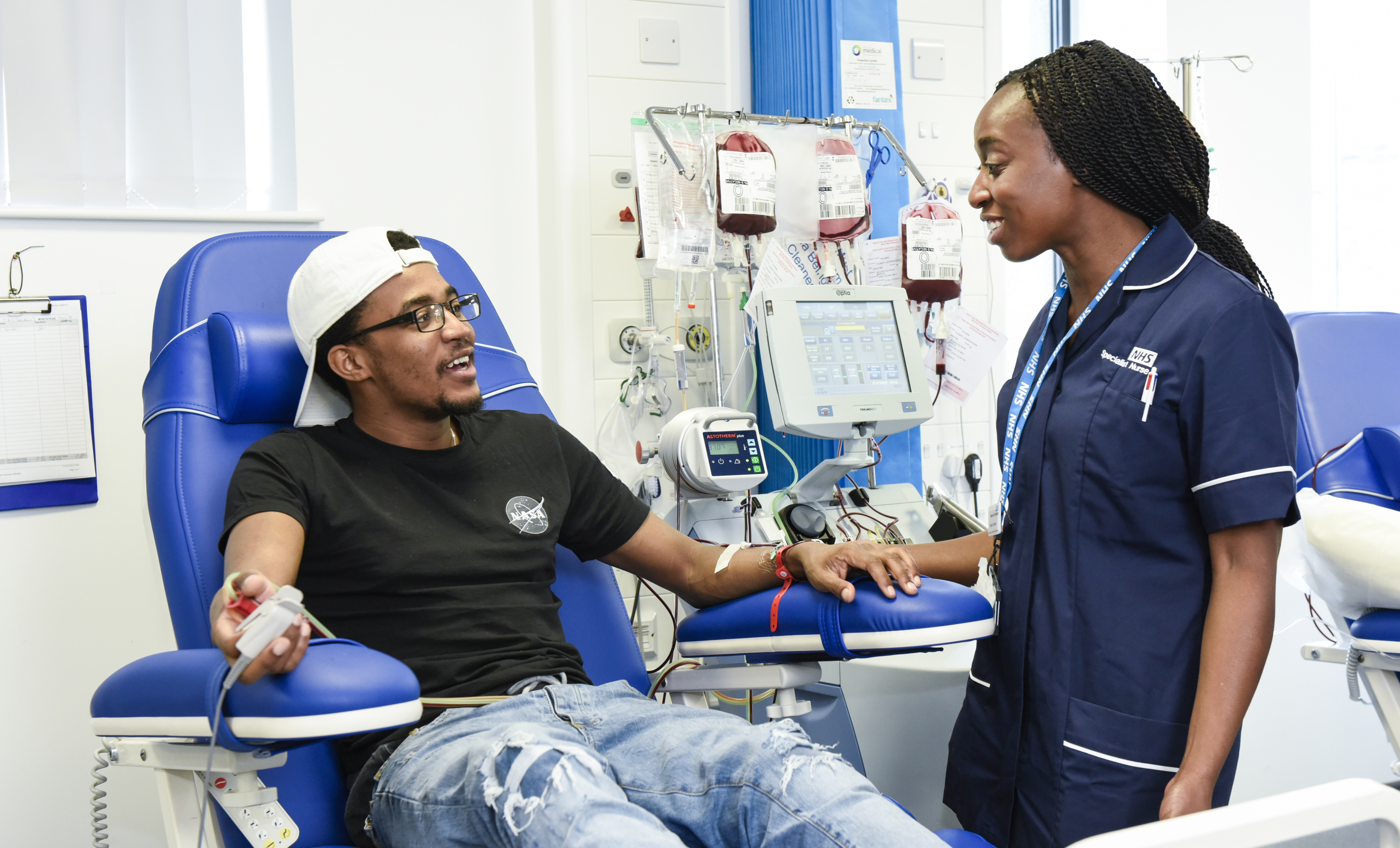 A patient and nurse chat while the patient receives apheresis