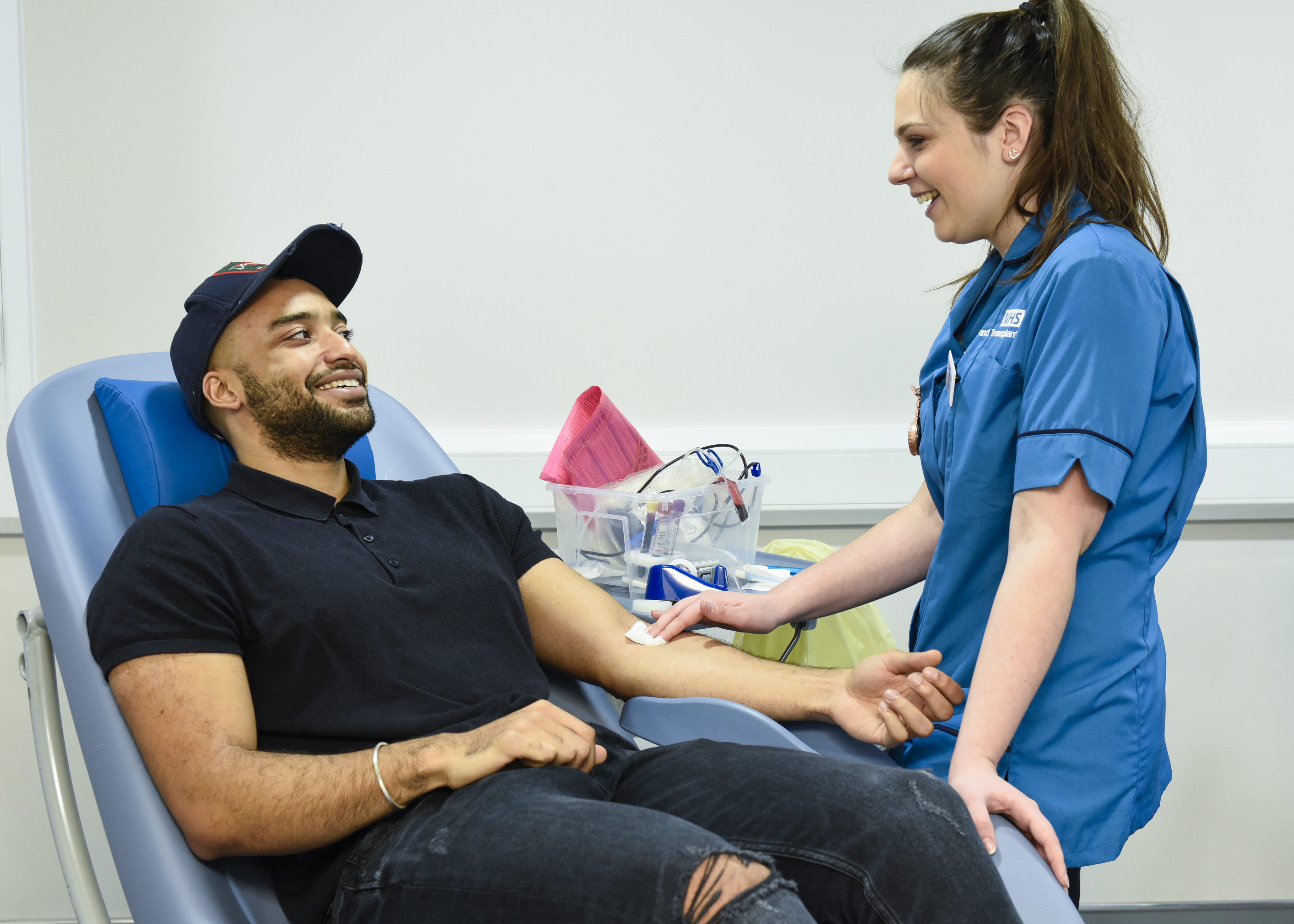 A donor carer swabs a donor's arm