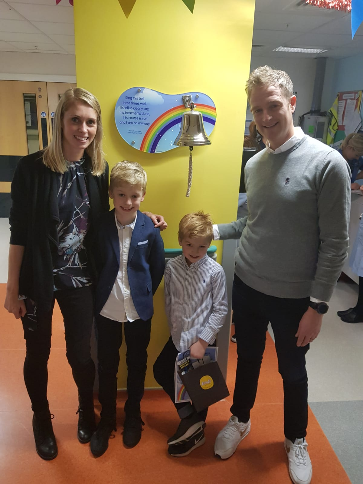 The Kidd family stand by an end of cancer treatment bell