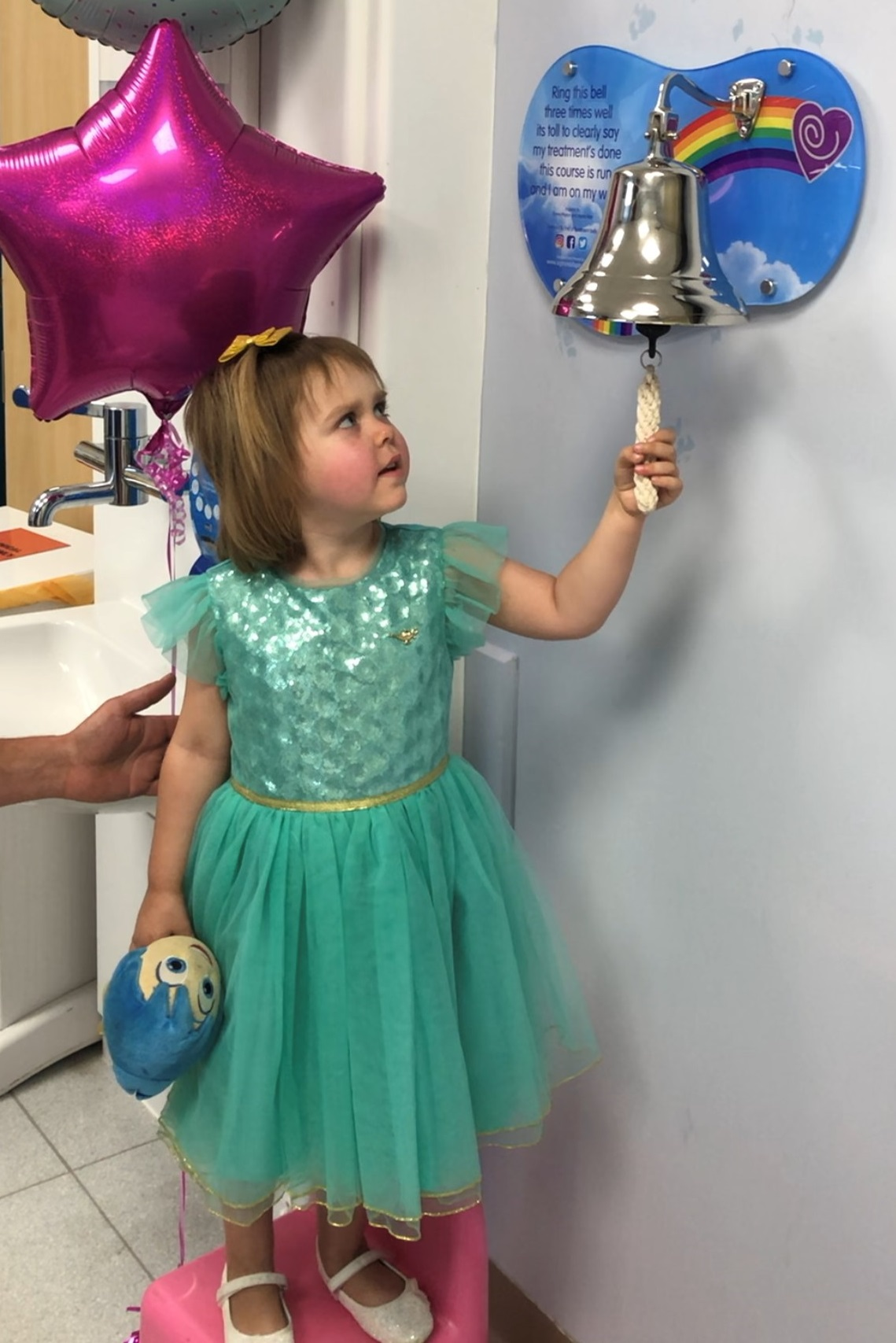 Sophia rings a silver bell that's mounted on a wall