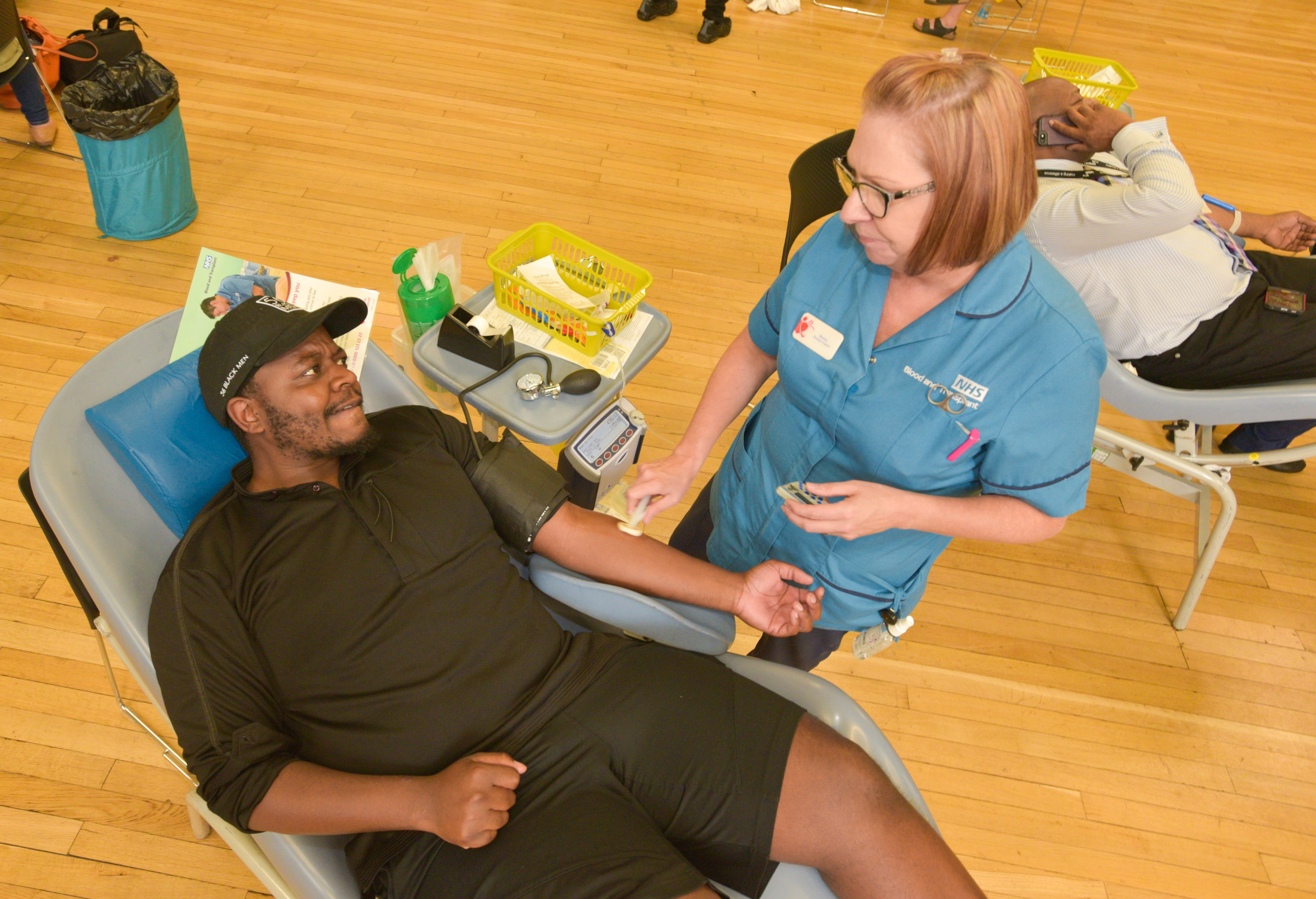 Bird's eye view of a donor carer cleaning a man's arm before he gives blood