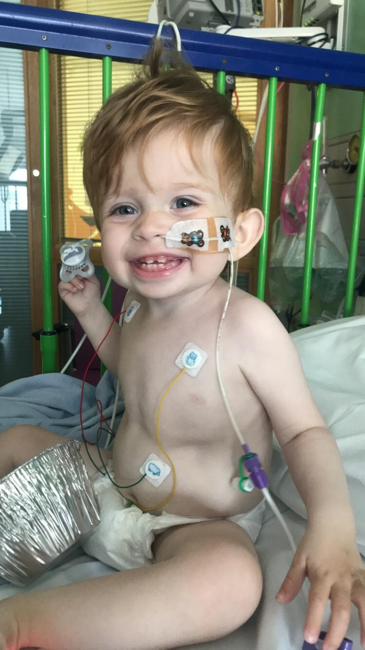 Grayson sits on a hospital cot with tubes attached to his nose and chest