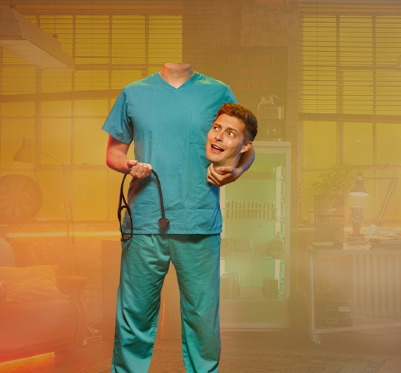 Dr Alex is wearing scrubs and is holding his head in his left hand and a stethoscope in his left