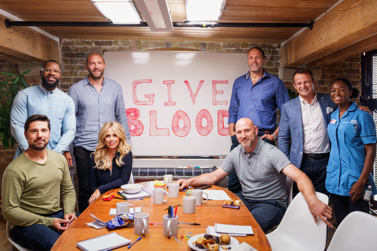 The BT Sport team show their support for blood donation by standing in front of a large Give Blood sign