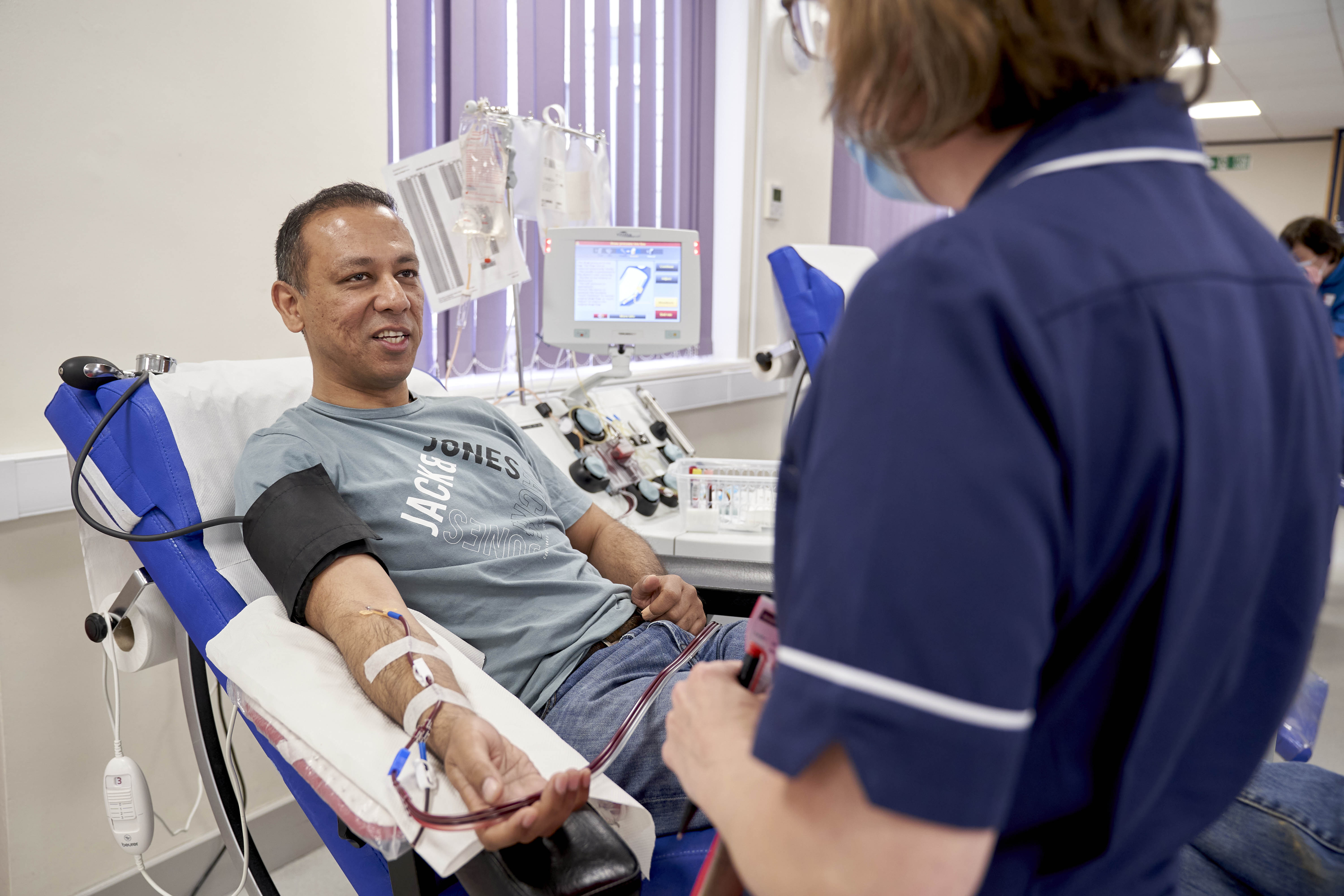 Dt Abhi Lal speaks to a donor carer while he donates plasma