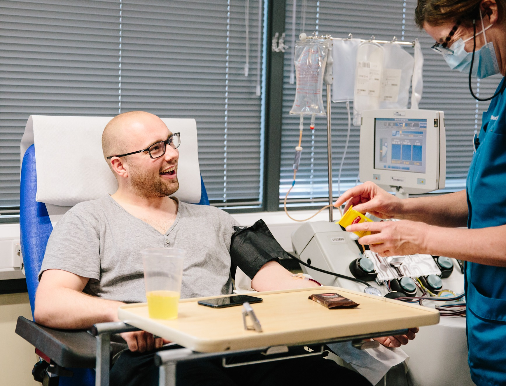 A donor talks to a donor carer as he gives plasma