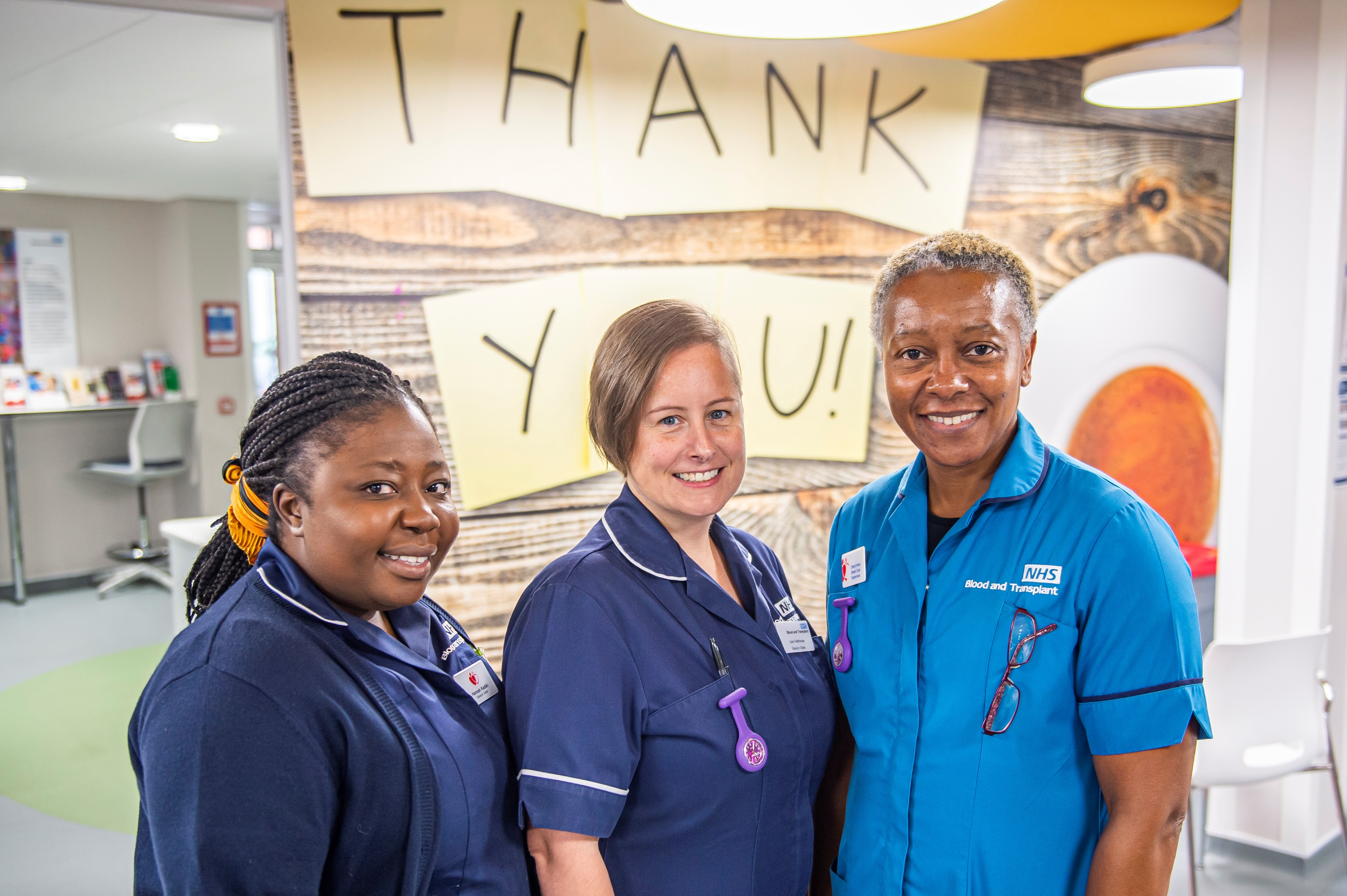 Three donors carers in front of a thank you sign