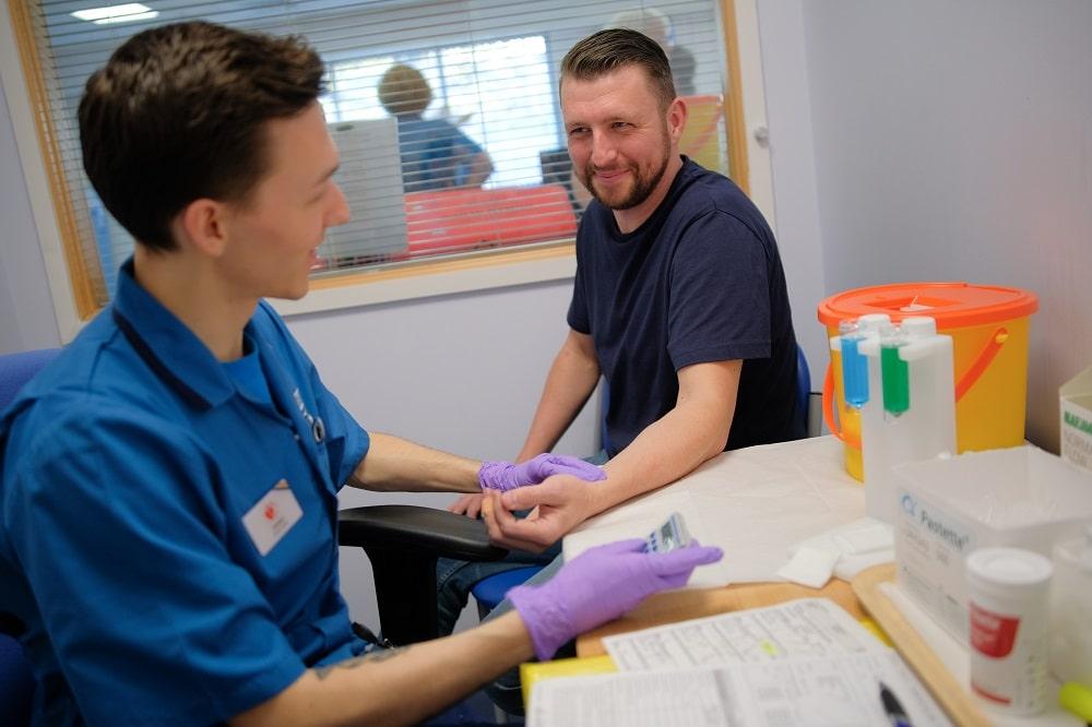 A donor carer checks a donor's pulse