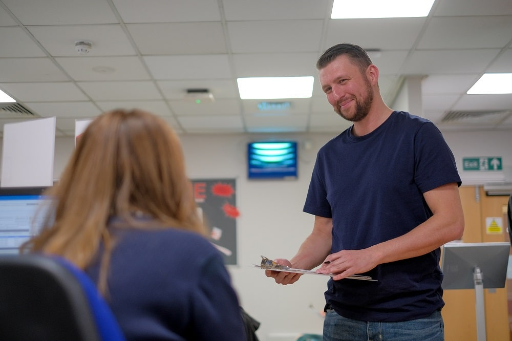 A donor holds a clipboard and speaks to a member of staff