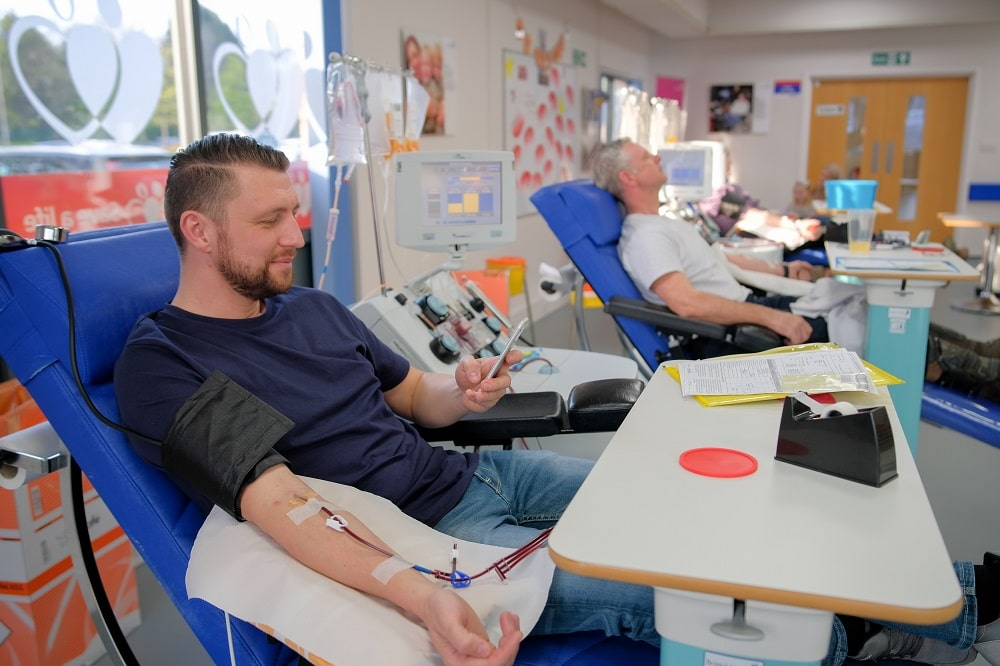 A donor uses his phone while he donates