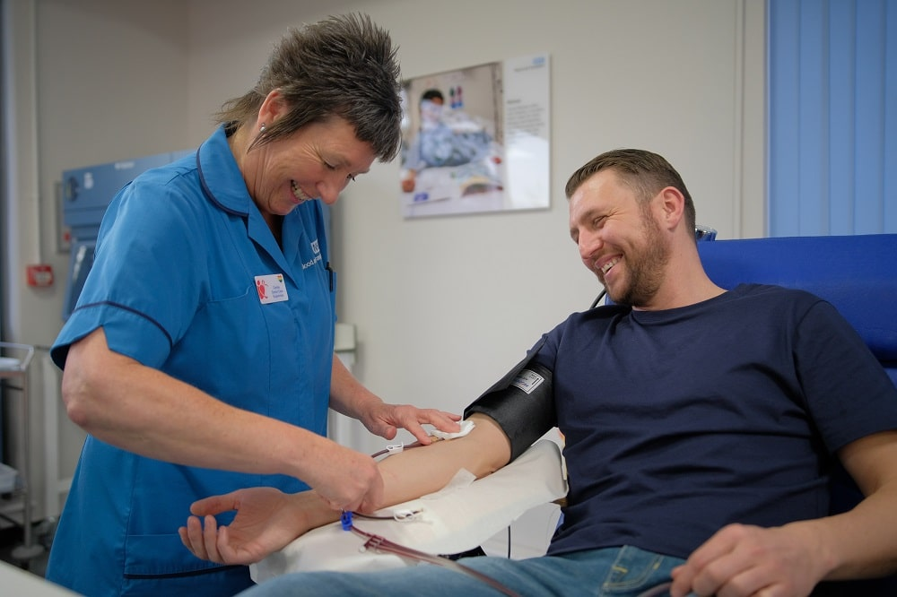 A donor carer removes a needle from Pete's arm