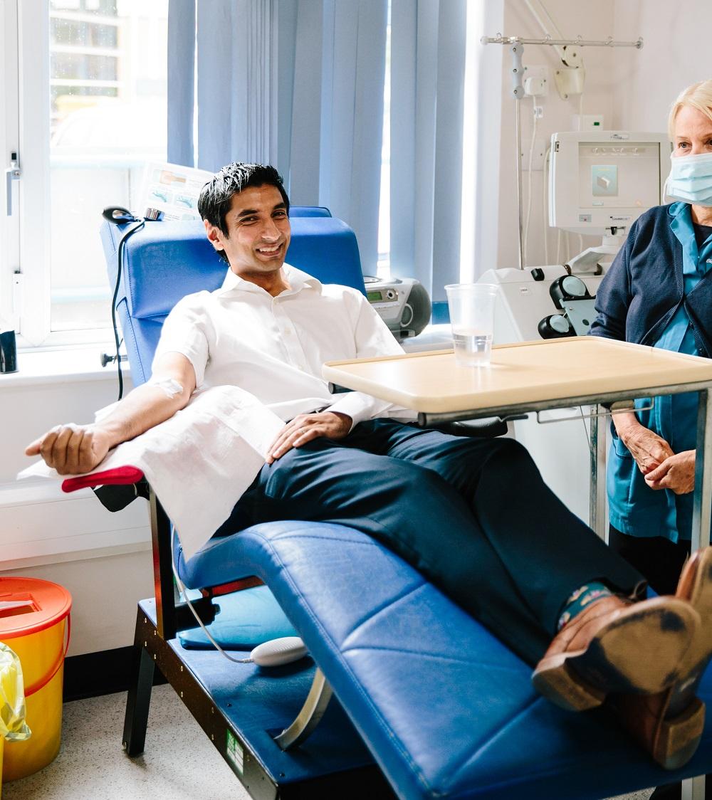 A man smiles while he donates plasma
