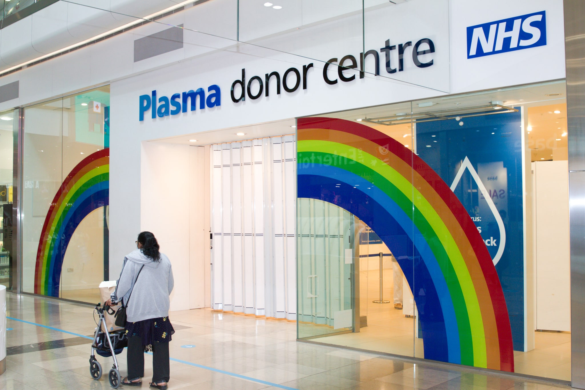 A woman with a pushchair walks past the outside of the donor centre