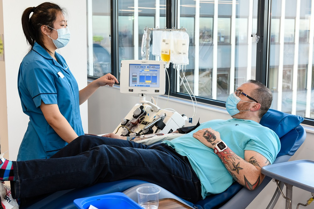 A man lies back in a chair while he donates plasma