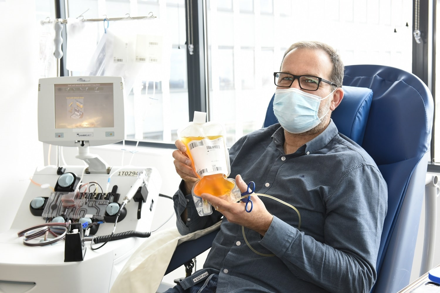 A man sitting in a donor chair holds a bag of his plasma