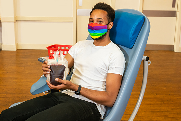 LGBT donor holding recently donated bag of blood in chair