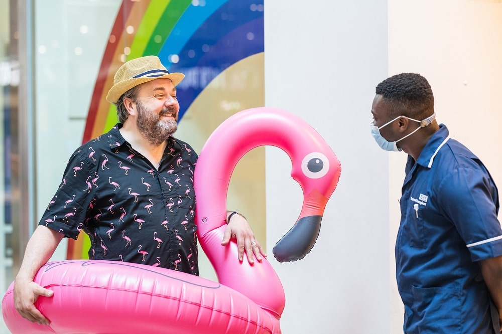 Hal is in a flamingo swimming ring. he is talking to a donor carer outside a donor centre.