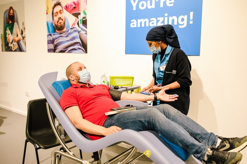 A blood donor talks to a donor carer while he donates