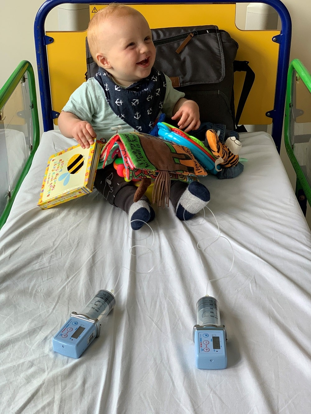 Sebastian is sitting on a hospital bed. He's playing with books and smiling while he has immunoglobulin infusions in his legs