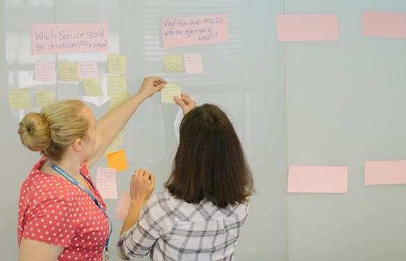 NHSBT staff arrange post-it notes during a planning meeting